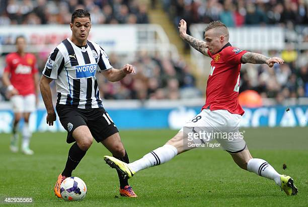 Hatem Ben Arfa of Newcastle looks to get past a tackle by Manchester United's Alexander Buttner during the Barclays Premier League match between...