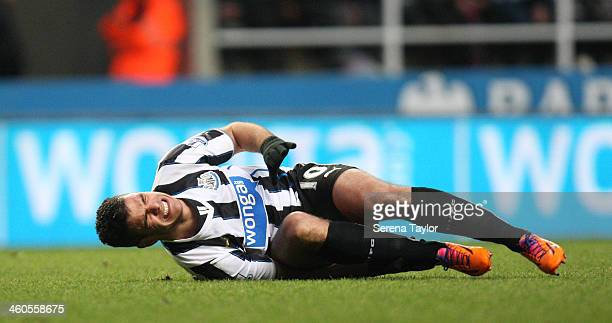 Hatem Ben Arfa of Newcastle rolls on the ground in pain after a challenge during the Budweiser FA Cup third round match between Newcastle United and...