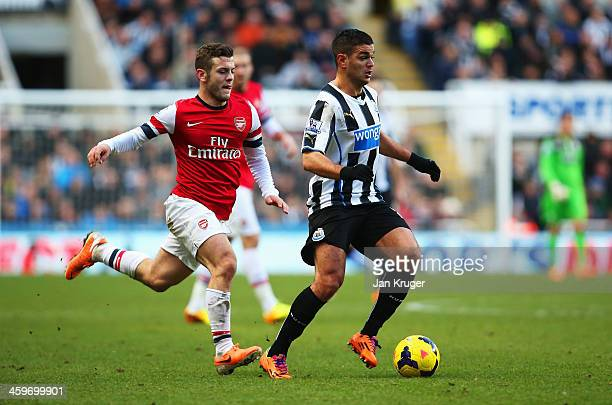 Hatem Ben Arfa of Newcastle United is closed down by Jack Wilshere of Arsenal during the Barclays Premier League match between Newcastle United and...