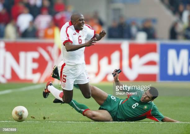 Hatem Trabelsi of Tunisia is takled by Noureddine Naybet of Morocco during the African Nations Cup 2004 Final match between Tunisia and Morocco at...