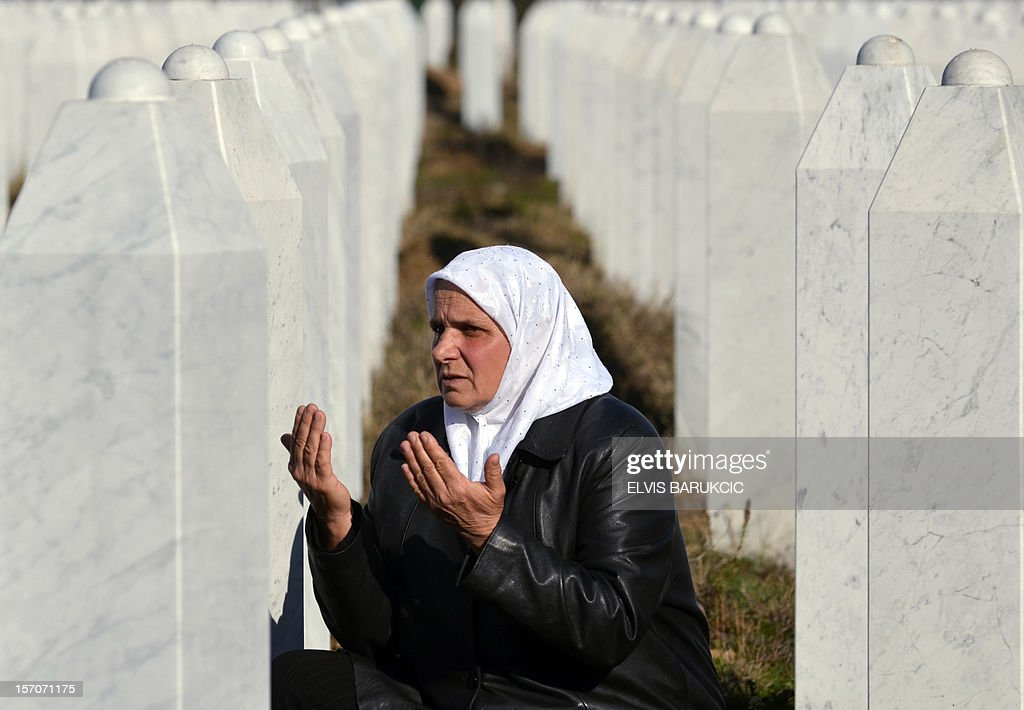 Hatidza Mehmedovic, a Bosnian Muslim woman survivor of the 1995 Srebrenica massacre, prays next to the graves of her husband and her two sons at the Memorial cemetery in Potocari, near Eastern-Bosnian town of Srebrenica, on November 28, 2012. AFP PHOTO ELVIS BARUKCIC