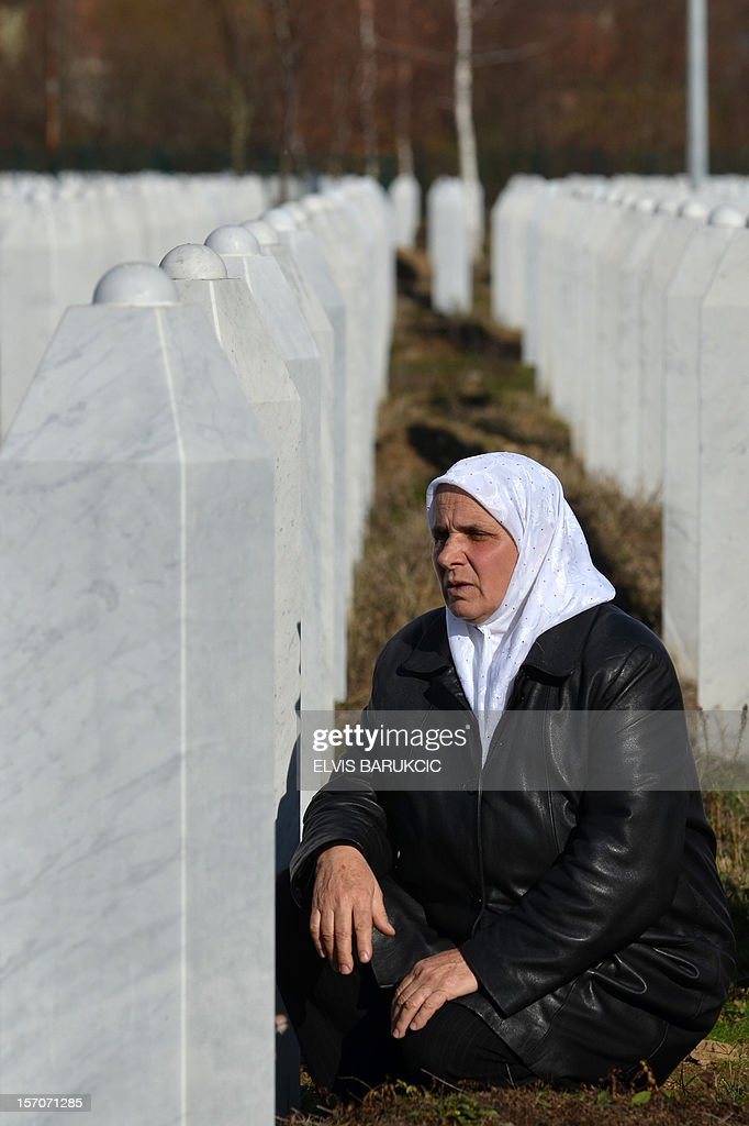 Hatidza Mehmedovic, a Bosnian Muslim woman survivor of the 1995 Srebrenica massacre, prays next to the graves of her husband and her two sons at the Memorial cemetery in Potocari, near Eastern-Bosnian town of Srebrenica, on November 28, 2012.