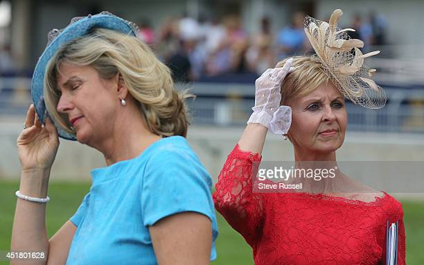 TORONTO ON JULY 6 Hats are braced in the wind at the 155th running of the Queen's Plate at Woodbine Race Track in Toronto July 6 2014