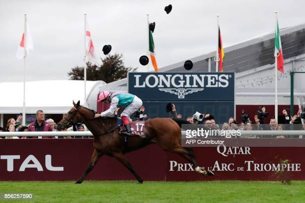 Hats are tossed into the air as jockey Frankie Dettori on his horse Enable crosses the finish line to win the 96th Qatar Prix de l'Arc de Triomphe...
