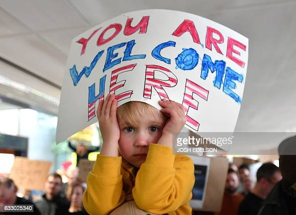 Hattie Burkeforeuic holds up a sign on her father's shoulders during a protest at San Francisco International Airport January 29 2017 US President...
