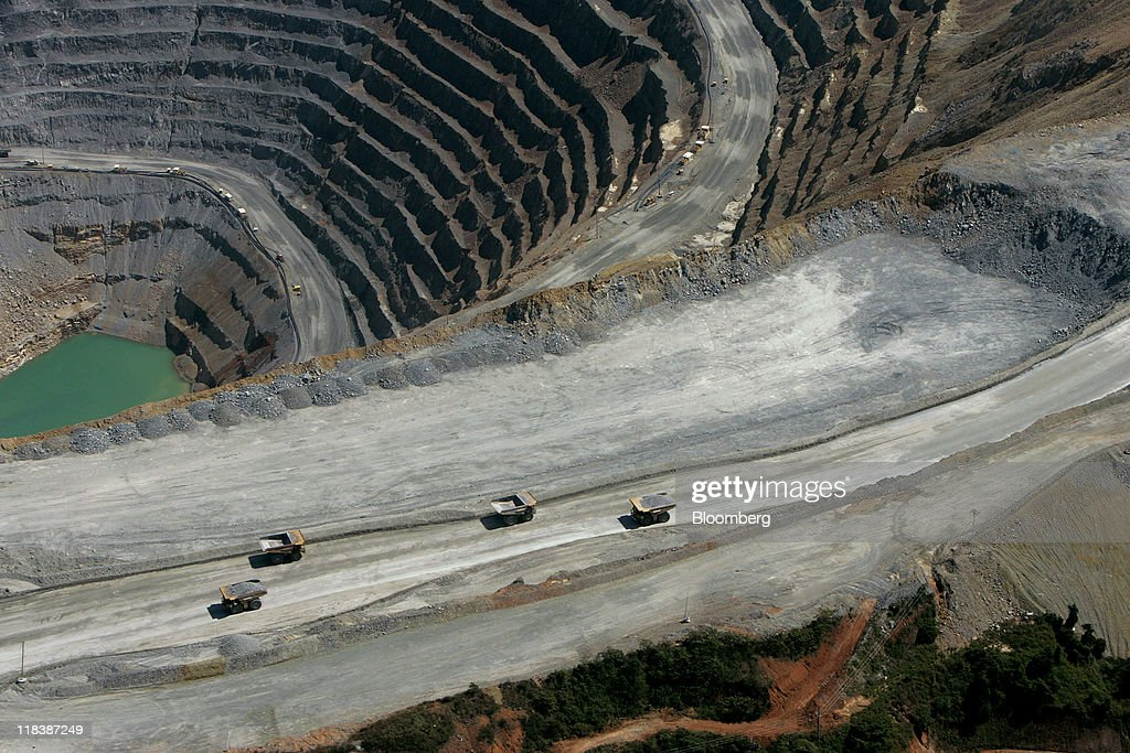 Haul trucks drive along a haulage road next to an open pit at the Batu Hijau copper and gold mine operated by PT Newmont Nusa Tenggara in Sumbawa, West Nusa Tenggara province, Indonesia, on Wednesday, June 29, 2011. PT Newmont Nusa Tenggara is a unit of Newmont Mining Corp. Photographer: Dadang Tri/Bloomberg via Getty Images