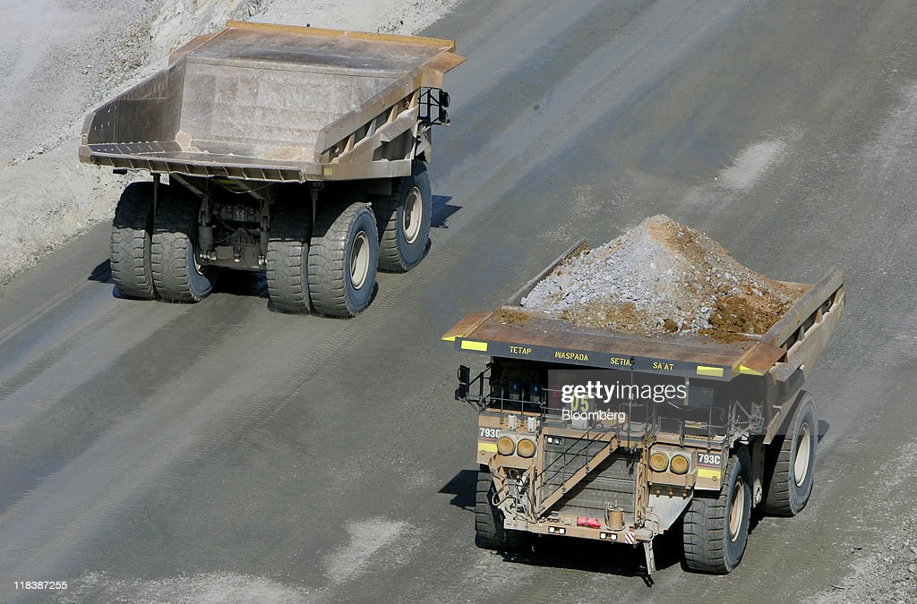 Haul trucks drive along access roads at the Batu Hijau copper and gold mine operated by PT Newmont Nusa Tenggara in Sumbawa, West Nusa Tenggara province, Indonesia, on Wednesday, June 29, 2011. PT Newmont Nusa Tenggara is a unit of Newmont Mining Corp. Photographer: Dadang Tri/Bloomberg via Getty Images