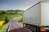 Delivery - Truck Transport. Tractor unit pulling a semi-trailer through a beautiful landscape.