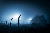 Abandoned old haunted house at night with fog around it.