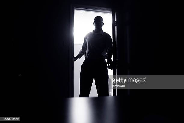 haunting office scene; man in doorway silhouetted