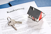 Haus mit Schlüssel und Kaufvertrag