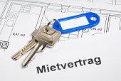 Hausschlüssel mit blauem Anhänger, Mietvertrag und Bauplan