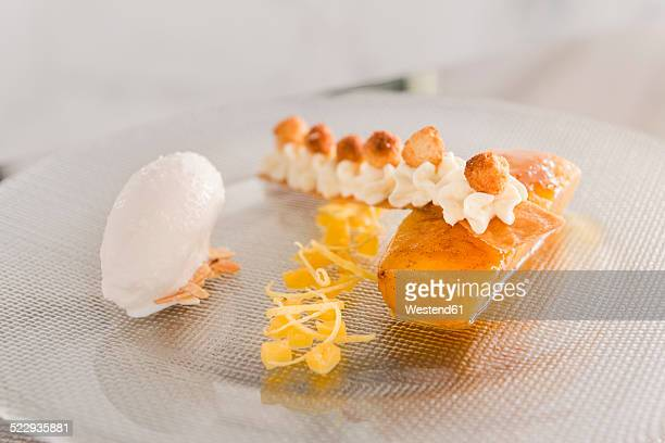 Haute Cuisine, Caramelized mango, Lemon mousse, Cream, Pineapple, Lemon peel and cinnamon on glass plate