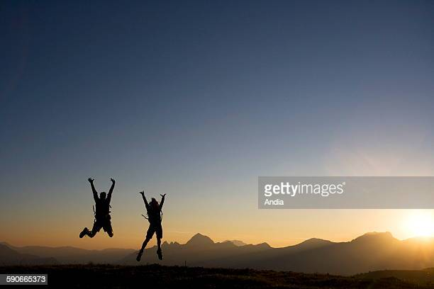 Haute Savoie department Couple of hikers jumping at sunset with mountains in the background