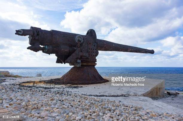 Havana 'El Morro' colonial Spanish fortress Antique war cannon pointing towards blue sea standing on a rough stone platform on a cloudy day