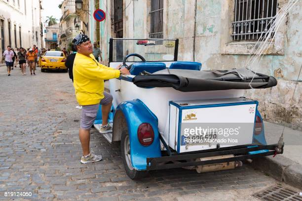 Havana 'Gran Car' and driver Man in yellow shirt and black bandana with a vintage blue and white car in a small cobbled street
