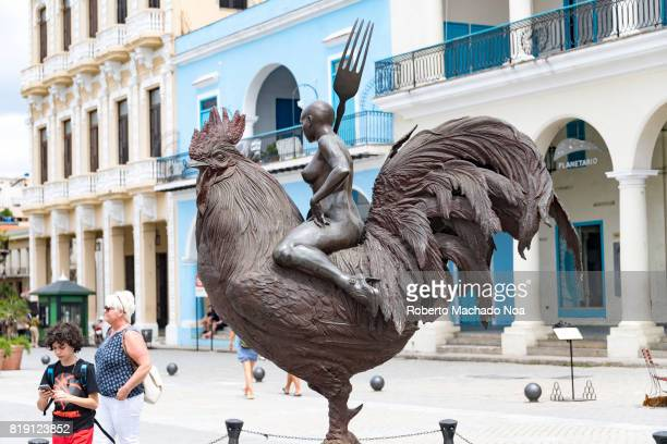 Havana 'Old Plaza' a famous tourism place Bronze sculpture of a bald and nude woman holding a fork sitting atop a rooster in a piazza