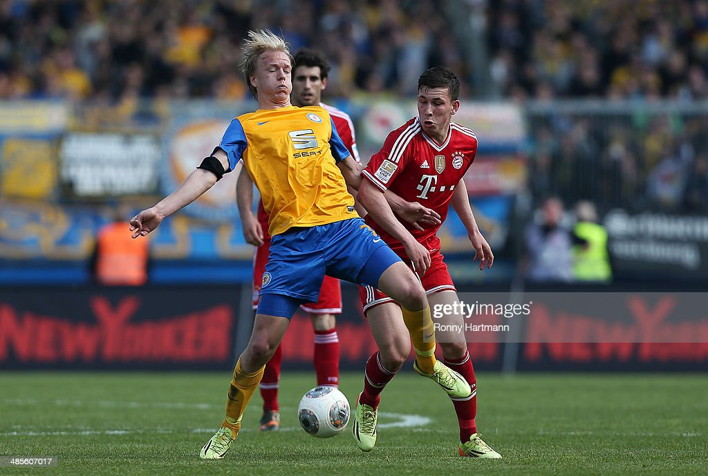 Havard Nielsen (L) of Braunschweig and Pierre-Emile Hoejbjerg of Muenchen vie for the ball during the Bundesliga match between Eintracht Braunschweig and FC Bayern Muenchen at Eintracht Stadion on April 19, 2014 in Braunschweig, Germany.