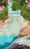 Havasu Creek plunges 100 feet over a travertine cliff  into a pure turquoise pool on the Havasupai Indian Reservation in the Grand Canyon.