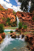 Havasu Falls plunges into a deep blue-green pool, with Cataract Canyon behind lit by the morning sun, on Havasupai Indian Reservation in the Grand Canyon.