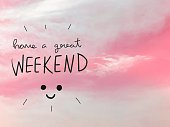 Have a great weekend word and smile face on pink sky background