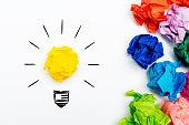 Crumpled paper light bulb over white background, surrounded by crumpled colorful paper. Idea concept.