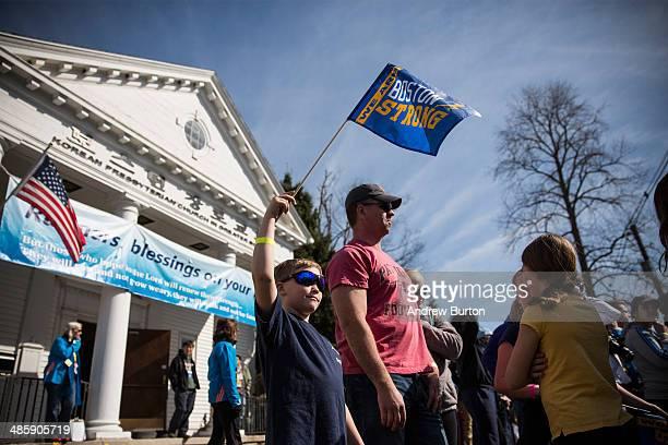 Haven Novack age 8 of Boxford MA waves a 'Boston Strong' flag at the beginning of the Boston Marathon on April 21 2014 in Hopkington Massachusetts...