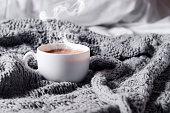 Having a cup of coffee on gray blanket in bed