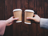 OLYMPUS DIGITAL CAMERAYoung couple holding paper cups of coffee against the wood background.