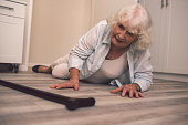 Shot of a senior woman falling on the floor of a retirement home and reaching for her cane