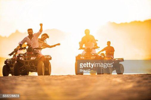 Having fun on quad bikes at sunset.