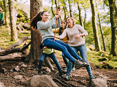 Teenage girl is being pushed on a rope swing in the woods by her family.