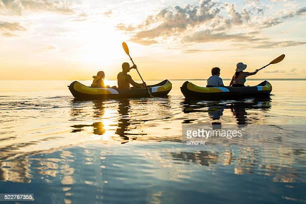Divirtiéndose kayak de mar en la puesta de sol