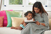 Pretty family of two having good time together: little daughter and her mother watching educational program on digital tablet while sitting on sofa