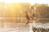 Having summer fun on the beach. Side view of beautiful and young woman jumping into the water from wooden pier with her young friend.