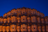 Hawa Mahal the most iconic symbol at Jaipur, capital city of Rajasthan, India. Dusk time with illuminated scenic facade and blue sky.