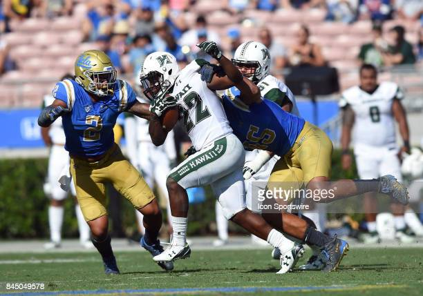 Hawai'i Diocemy Saint Juste runs the ball and is tackled by UCLA Josh Woods and UCLA Jaelan Phillips during a college football game between the...