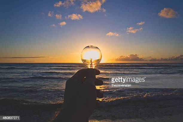USA, Hawaii Islands, View of hand holding lightbulb at sunset