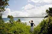 USA, Hawaii, Kauai, North Shore, woman overlooking beach, rear view