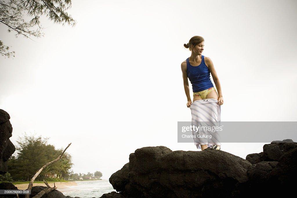 USA, Hawaii, Kauai, woman removing skirt atop rock on beach : Stock Photo