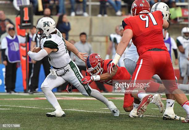 Hawaii quarterback Dru Brown attempts to escape Fresno State defensive back Stratton Brown during the game between the Fresno State Bulldogs and the...