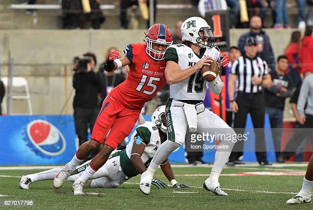 Hawaii quarterback Dru Brown is pursued by Fresno State defensive back Stratton Brown during the game between the Fresno State Bulldogs and the...