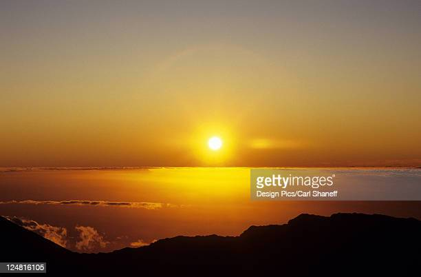 Hawaii, Sunball sinking into the horizon over the ocean, view from mountaintop