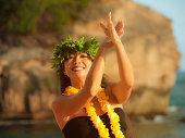 A beautiful Hawaiian Hula dancer dancing on the beach of the tropical Hawaiian islands. She is wearing a contemporary Hula dance dress with a lei and flower headdress. Photographed in horizontal forma