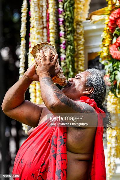 Hawaiian man blows into a conch shell in front of the King Kamehameha Statue in Honolulu Hawaii Oahu during a traditional Hawaiian ceremony...