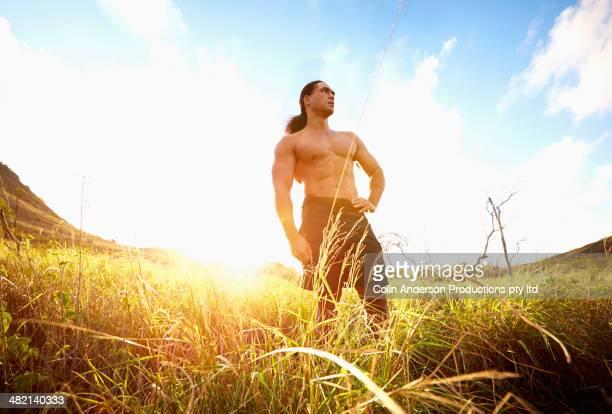 Hawaiian man standing in rural field