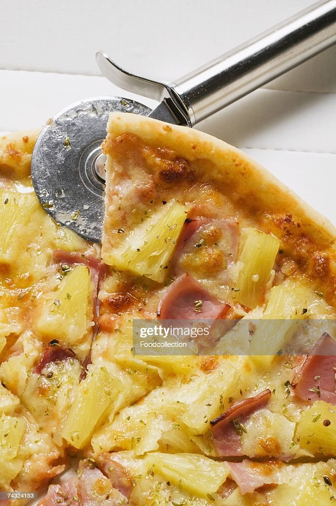 Hawaiian pizza, sliced, in pizza box with pizza cutter : Stock Photo
