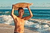 """Photo of a local Hawaiian surfer standing with his surf board over-head; Kauai, HI."""