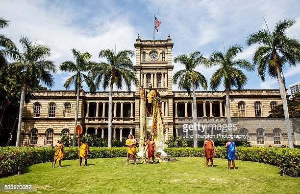 Hawaiians in traditional dress stand in with respect front of the King Kamehameha Statue draped in Flower Lei in Honolulu Hawaii on the Island of...