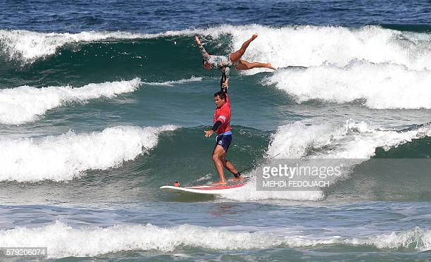 US Hawaii's Kalani Vierra and Krystl Apeles compete in the International Tandem Surfing Championship on July 23 2016 in Biscarrosse / AFP / MEHDI...